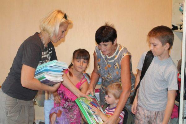 Многодетная семья получает натуральную помощь перед новым учебным годом